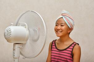 扇風機で涼む女の子の写真素材 [FYI02992648]