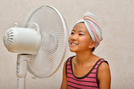 扇風機で涼む女の子の写真素材 [FYI02992650]