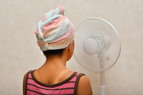 扇風機で涼む女の子(後姿)の写真素材 [FYI02992653]