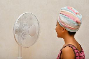 扇風機で涼む女の子(後姿)の写真素材 [FYI02992655]