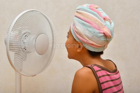 扇風機で涼む女の子(後姿)の写真素材 [FYI02992656]
