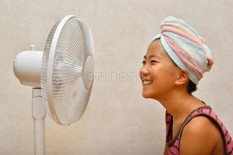 扇風機で涼む女の子の写真素材 [FYI02992657]