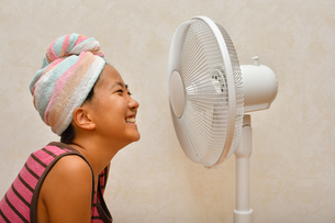 扇風機で涼む女の子の写真素材 [FYI02992660]