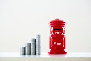 積み上げられた一円硬貨とポスト型貯金箱の写真素材 [FYI02993565]