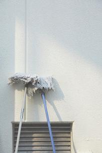 白い壁に立てかけられた2本のモップの写真素材 [FYI02993712]