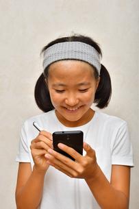 スマートフォンを操作する女の子の写真素材 [FYI02994171]