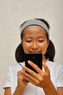 スマートフォンを操作する女の子の写真素材 [FYI02994174]