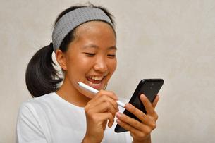 スマートフォンを操作する女の子の写真素材 [FYI02994178]