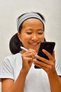 携帯電話を操作する女の子の写真素材 [FYI02994188]