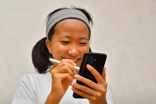スマートフォンを操作する女の子(タッチペン)の写真素材 [FYI02994189]