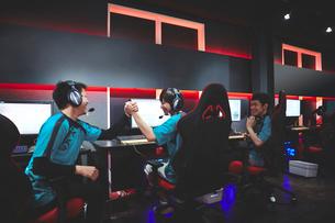 eSportsカフェでガッツポーズをする男性プレイヤーチームの写真素材 [FYI02994394]