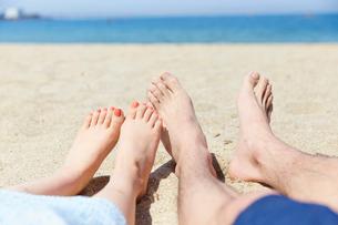 砂浜に座る男女の足元の写真素材 [FYI02995242]