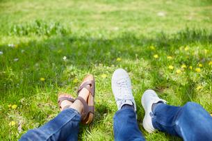 草原で日向ぼっこをする男女の足元の写真素材 [FYI02995255]