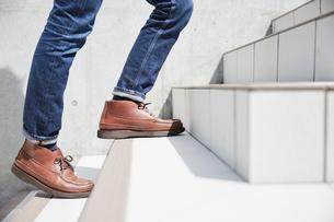 白い階段を上がる男性の足元の写真素材 [FYI02995261]