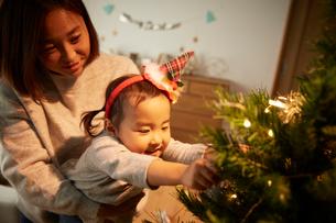 クリスマスツリーの飾り付けをする親子の写真素材 [FYI02995280]