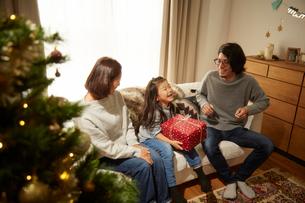 両親からクリスマスプレゼントをもらって喜ぶ女の子の写真素材 [FYI02995295]