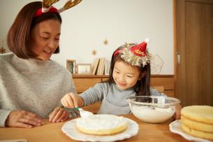 クリスマスケーキを作っている親子の写真素材 [FYI02995300]