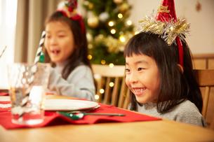 家族でクリスマスパーティをしてたのしそうな姉妹の写真素材 [FYI02995304]