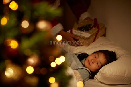 寝ている女の子の枕元にプレゼントを置くサンタクロースの手の写真素材 [FYI02995327]