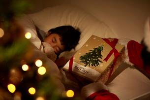 寝ている女の子の枕元にプレゼントを置くサンタクロースの手の写真素材 [FYI02995328]