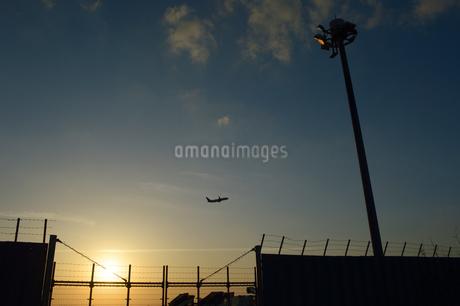 夕日のフェンス越しの滑走路と離陸する旅客機の写真素材 [FYI02995590]