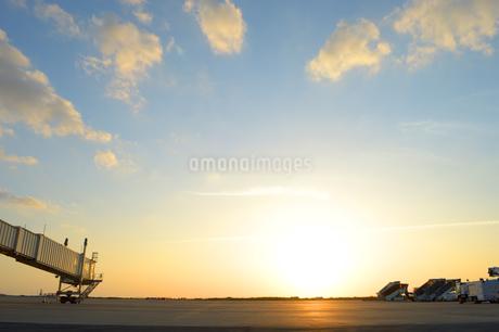 夕日を浴びる滑走路のタラップ車とボーディングブリッジの写真素材 [FYI02995600]