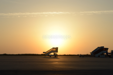 夕日の滑走路を走るタラップ車の写真素材 [FYI02995604]