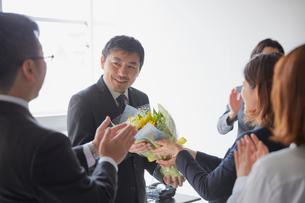 退職祝いに花束を送る社員とそれを受け取る上司の写真素材 [FYI02996152]