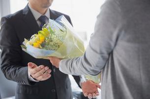 退職祝いに花束を送る社員とそれを受け取る上司の写真素材 [FYI02996153]