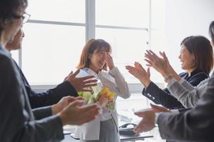 寿退社を祝う社員と涙を流す女性社員の写真素材 [FYI02996160]