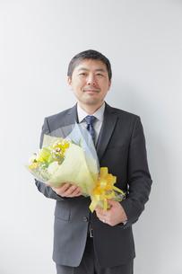 退職祝いの花束を抱える男性社員の写真素材 [FYI02996168]