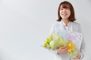 寿退社のお祝いで花束を抱える女性社員の写真素材 [FYI02996174]