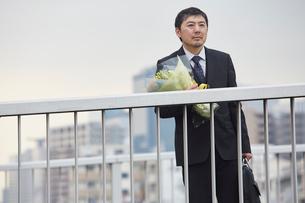 退職をして花束を抱えながら途方に耽る男性社員の写真素材 [FYI02996178]