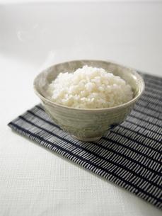茶碗に盛られた湯気のたつ白米の写真素材 [FYI02997758]