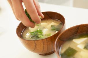 味噌汁にネギを盛る女性の手元の写真素材 [FYI02997783]