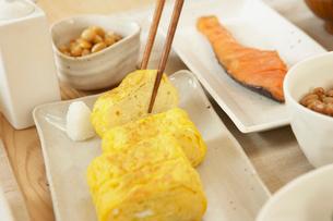 玉子焼きを摘む箸と和食のおかずの写真素材 [FYI02997799]