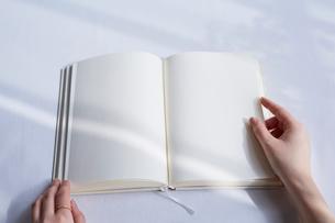 白いテーブルの上に開かれた白紙の本と手の写真素材 [FYI02998305]