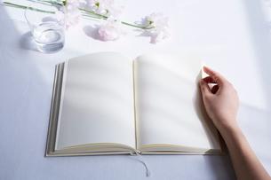白いテーブルの上に開かれた白紙の本と手の写真素材 [FYI02998314]