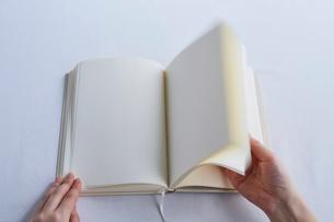 白いテーブルの上に開かれた白紙の本と手の写真素材 [FYI02998318]
