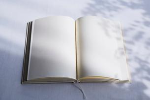白いテーブルの上に開かれた白紙の本の写真素材 [FYI02998323]