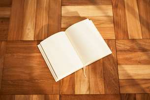 組み木の床に開いておいてあるノートの写真素材 [FYI02998324]