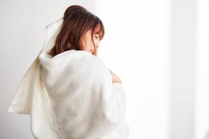 白壁前で白いバスタオルで頭を拭く女性の写真素材 [FYI02998327]