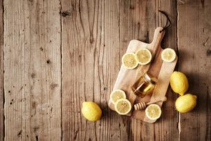 カッティングボードの上に置かれた蜂蜜と輪切りのレモンの写真素材 [FYI02998461]