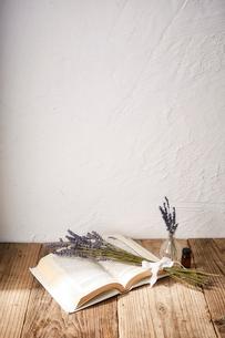 白い本の上に置かれたラベンダーのドライフラワーとアロマオイルの写真素材 [FYI02998471]