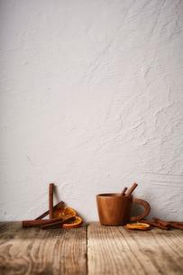 木天板の上のシナモンスティックとドライオレンジと木のカップの写真素材 [FYI02998472]