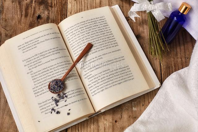 洋書の上に置かれたラベンダーの花とスプーンの写真素材 [FYI02998477]
