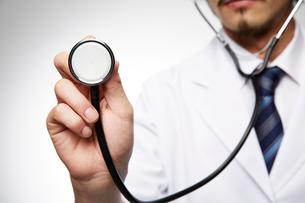 聴診器を向ける男性医師の手元の写真素材 [FYI02998483]