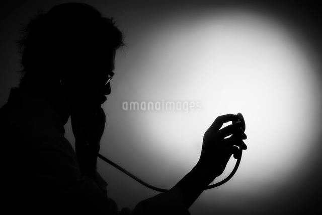 聴診器を当てる男性医師の影の写真素材 [FYI02998484]