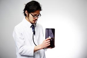 タブレットに聴診器を当てる男性医師の写真素材 [FYI02998493]