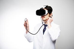 VRゴーグルをつけて聴診器を当てる男性医師の写真素材 [FYI02998494]